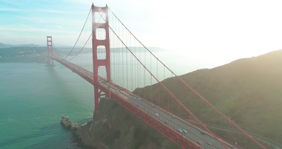 Aerial view of the Golden Gate landmark with San Francisco green hills on a background. Drone flight outbound the tower of the red bridge with the sunset view above the Pacific Ocean, West coast. 4K