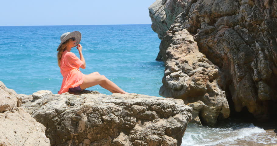 Young pretty woman in swimsuit and coverup sitting on the rocks near the sea #1010012438