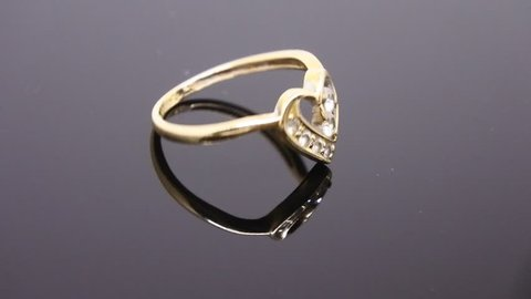 wedding ring swaying on dark background (footage)