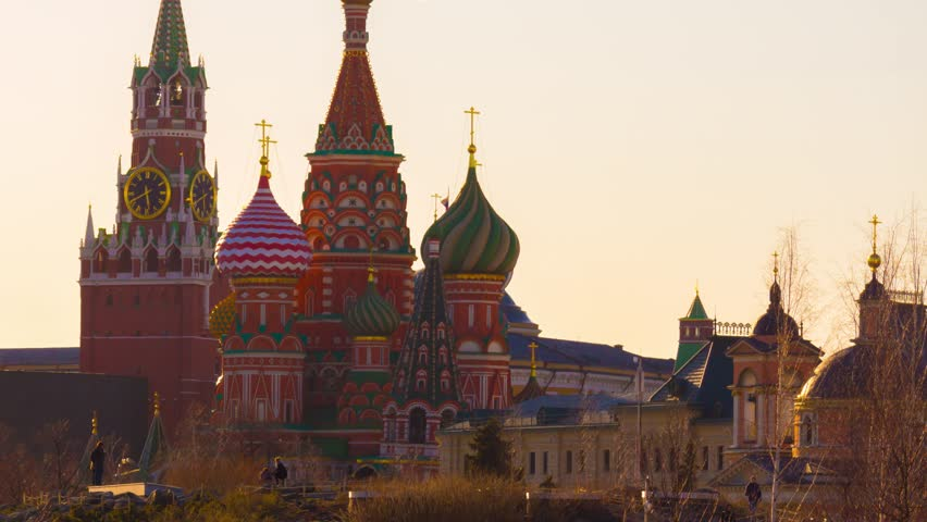 Moscow Saint Basil's Cathedral and Kremlin Main Clock named Kuranti on Spasskaya Tower. Golden sunset colors. Telephoto. Panning. Timelapse.