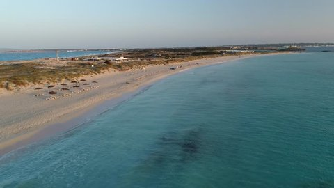 Sunloungers on a deserted Playa Illetas beach at sunset in Formentera with the camera moving over crystal clear waters