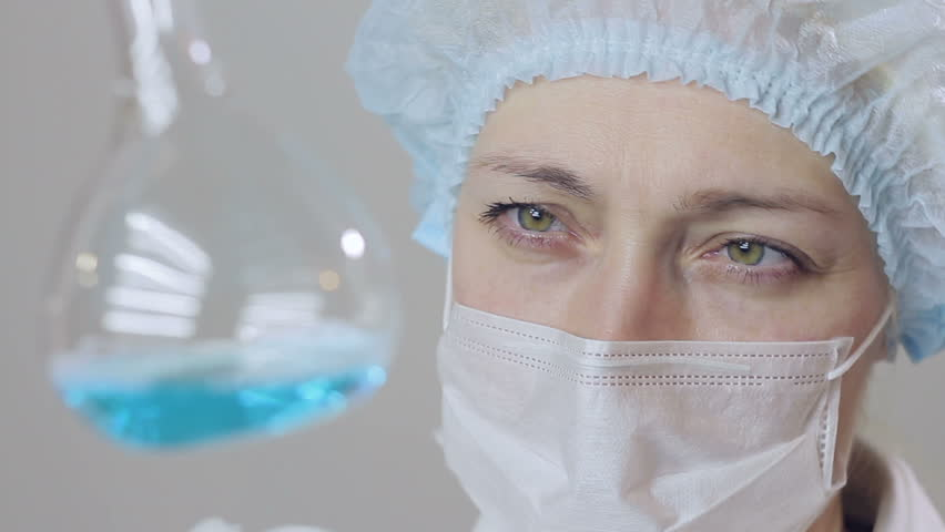 Closeup of a female scientist doctor analyzing cells of a fluid virus in a professional laboratory