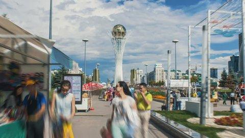 Kazakhstan, Astana, July 19, 2017. People walk through the Nurljole boulevard. Astana-Bayterek. Baiterek Tower.  Day time motion timelapse at the Astana, with a cloudy sky.