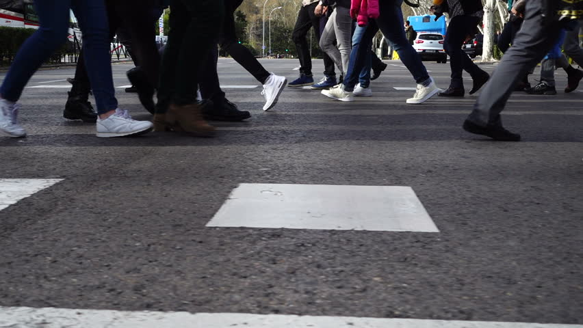 People cross the road on the crosswalk. Slow motion.