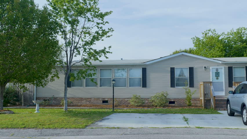 Establishing shot of a manufactured home with an SUV car in the driveway and a couple of trees with green leaves during the day - dolly shot