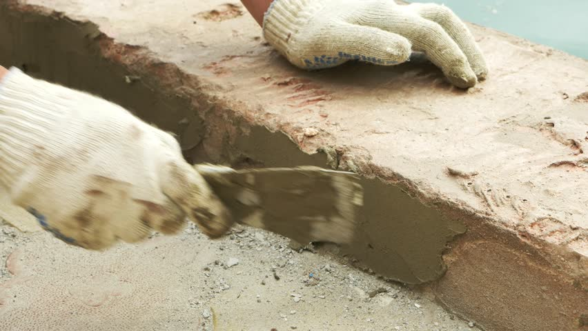 spatula and bucket with mortar on the construction site. the builder finishes the surface with plaster. 4k. pool repair.