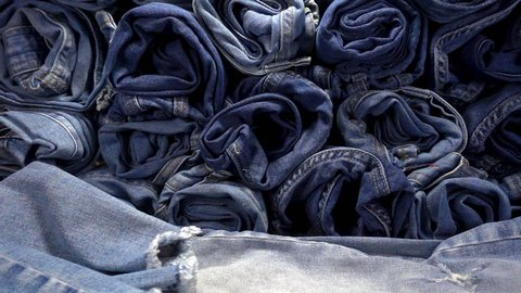 Slow Motion of falling jeans on a pile of denim  trousers.