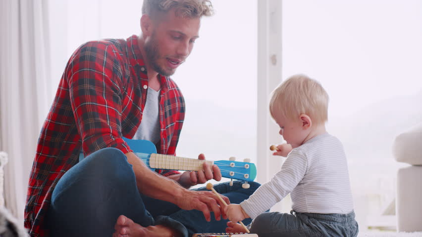 Dad and toddler son playing with instruments, close up