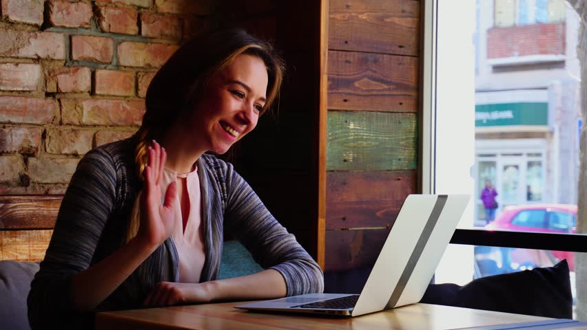 Pretty female person making video call to boyfriend by laptop, showing thumbs up, blowing kiss and waving farewell. Concept of communicating with close people by wireless Internet. Young woman resting | Shutterstock HD Video #1010139278