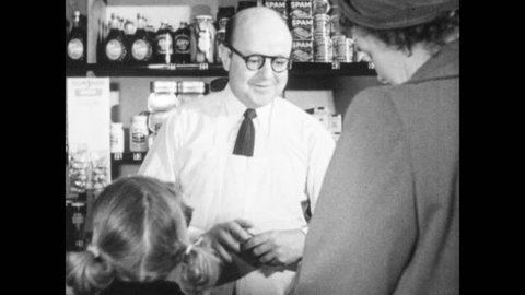 1940s: Customer buys items at store, leaves. Girl looks at lollipops on display, man nods at girl, hands her lollipop, pats her shoulder. Man holds social security card.