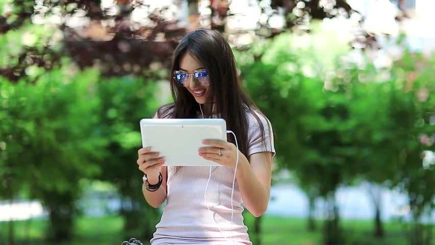 Woman with tablet computer. Beautiful girl uses tablet computer. Attractive girl hold in hands white tablet pc. Woman with tablet pc communicates through videochat | Shutterstock HD Video #1010156648