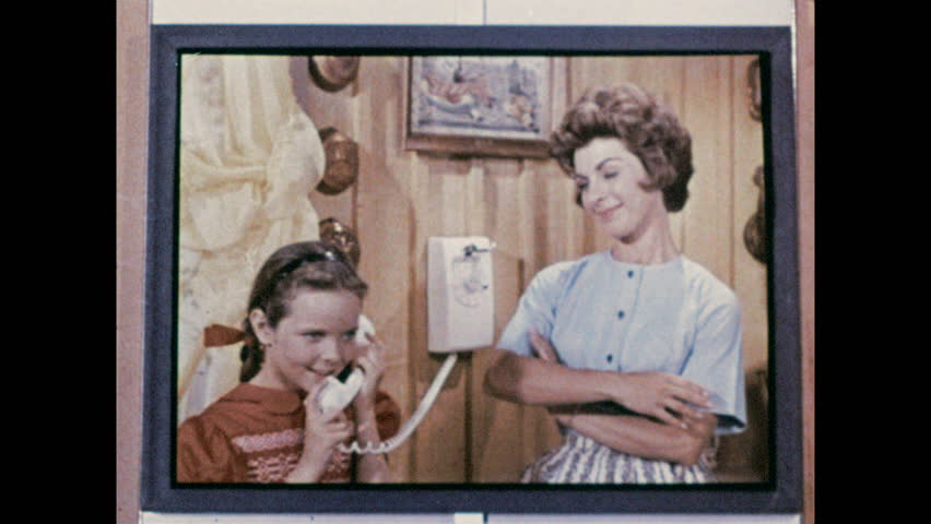 1960s: Image on screen, girl talks on phone next to woman. Close up of woman talking. Image on screen, woman on phone, zoom in to hand dialing phone. #1010158628