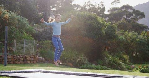 Little girl happily jumping on trampoline in garden 4K 4k