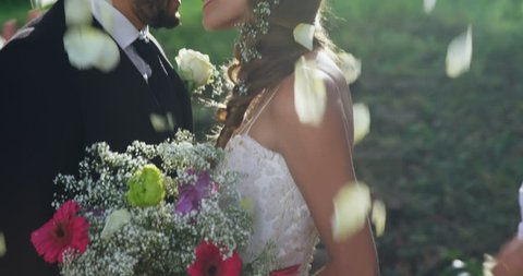 Close-up of Caucasian bride and groom kissing and in background guests toss petals.