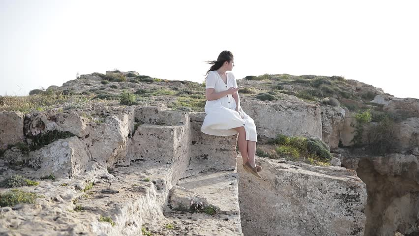 Young girl does photo near to the blue sea sitting on a mountain Woman Watching Sunset. Takes Panorama Photos On Phone. Hair in the Wind | Shutterstock HD Video #1010172158