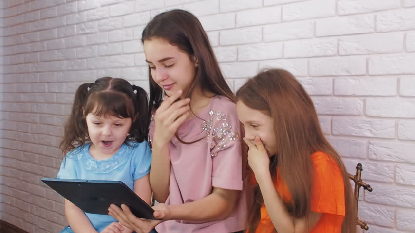The girls are watching the video on the Internet. Sisters with a tablet laugh. | Shutterstock HD Video #1010176028