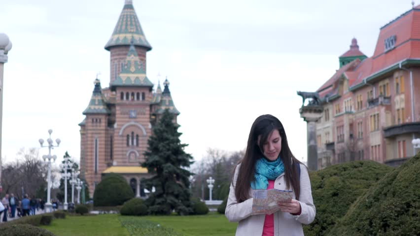 SLOW MOTION: Girl looking at map of Timisoara. Young brunette woman standing on a city square in Timisoara, Romania, looking at the map.