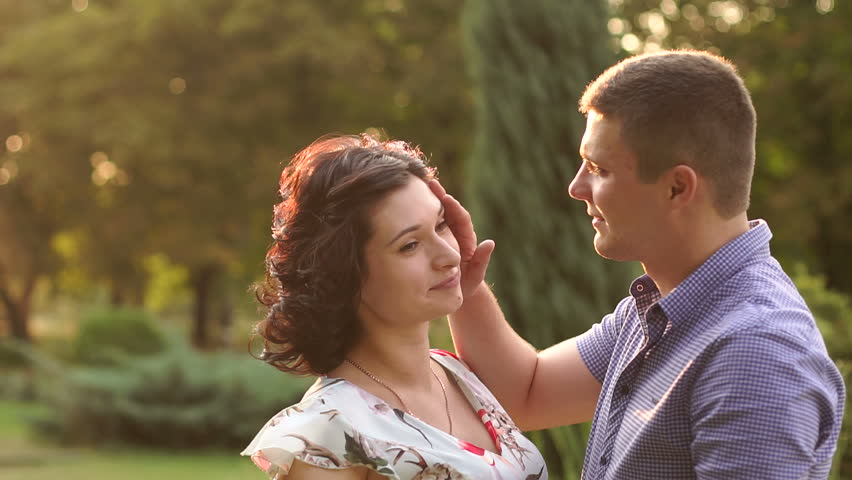 A pregnant woman and her husband walking in summer Park at sunset. Slow motion. Happy family expecting a baby. Portrait of happy man embracing his pregnant wife.   Shutterstock HD Video #1010185778