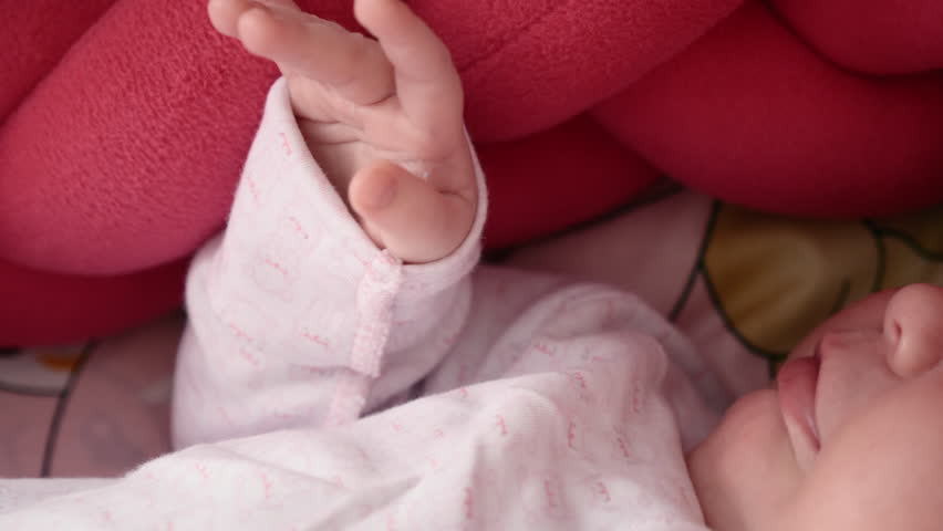 A cute newborn is sleeping in a wicker cradle. Close-up of the fingers of a hand   Shutterstock HD Video #1010198858