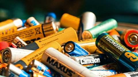 VINNITSA, UKRAINE - APRIL 2018: Used batteries from different manufacturers, waste, collection and recycling, high danger for the environment. Batteries background