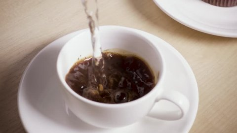 Hot water is poured into a mug on a saucer with instant coffee slow motion