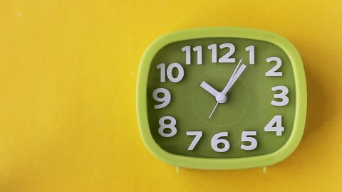 Green clock with white numbers and arrows on yellow background, Time Lapse