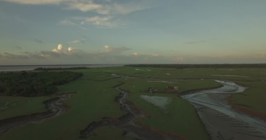 Aerial tilt down of Marajo Island Amazon River inlets and tributaries with a small stilt house in the background at low tide