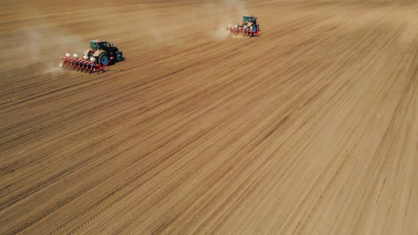 Aerial drone shot of a farmers in two tractor seeding, sowing agricultural crops at field
