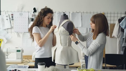 Creative fashion designers are pinning cut out pieces of fabric to mannequin while sewing women's garment in modern studio. Ladies are concentrated on their work.