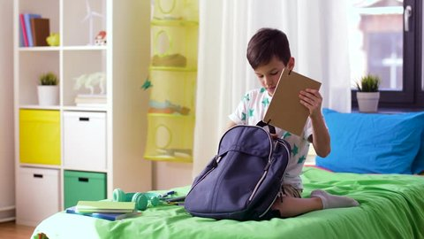 education, childhood and people concept - boy packing schoolbag with school supplies at home