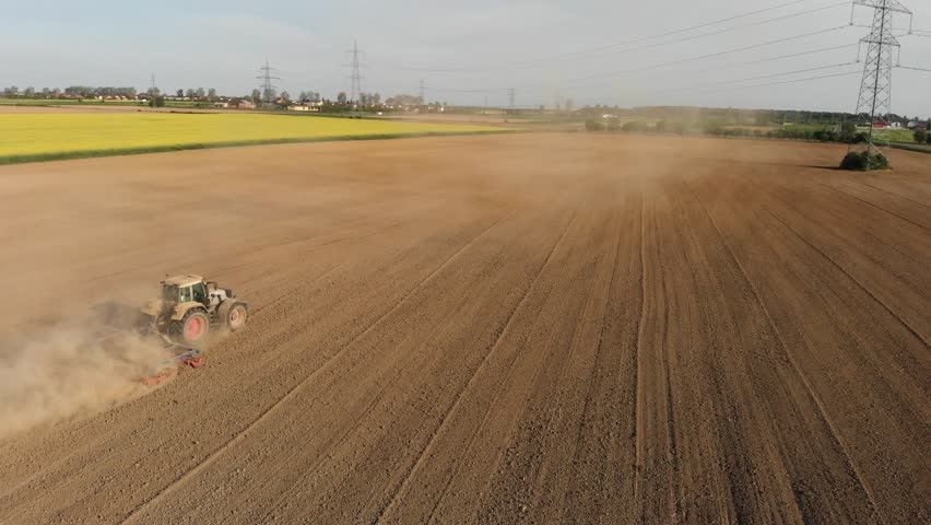 Aerial of tractor on field in dust (top view from height)  | Shutterstock HD Video #1010258558