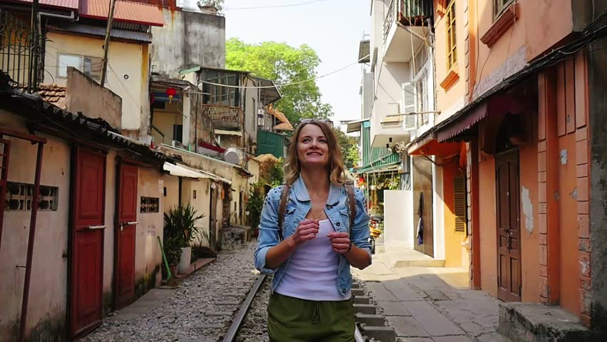 A young traveler woman runs the old city, by rail road and stop and start spinning looks around. Vietnam, Hanoi city, Train street. Slow motion video
