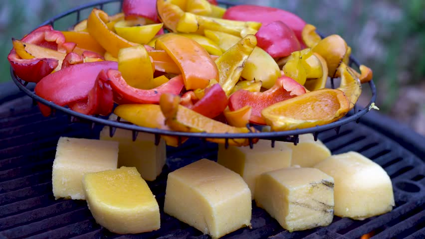 Orange, red, and yellow bell peppers on a grill with polenta grilling below.