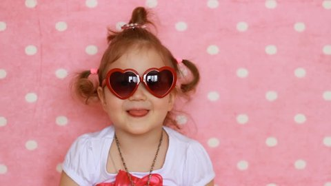 Funny child smiles, laughs and shows tongue. Pink background. Cute little girl in red sunglasses in the shape of hearts. Glamour. Fashion