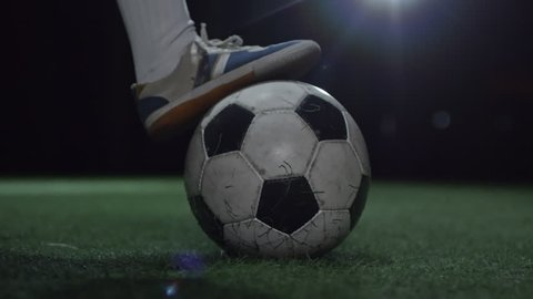 Closeup shot of feet of junior soccer player holding foot on ball on artificial turf in dark arena and then kicking it