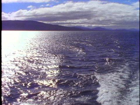 ARGENTINA, 1998, Crossing Andes mountain lake, POV from boat, the stern with wake