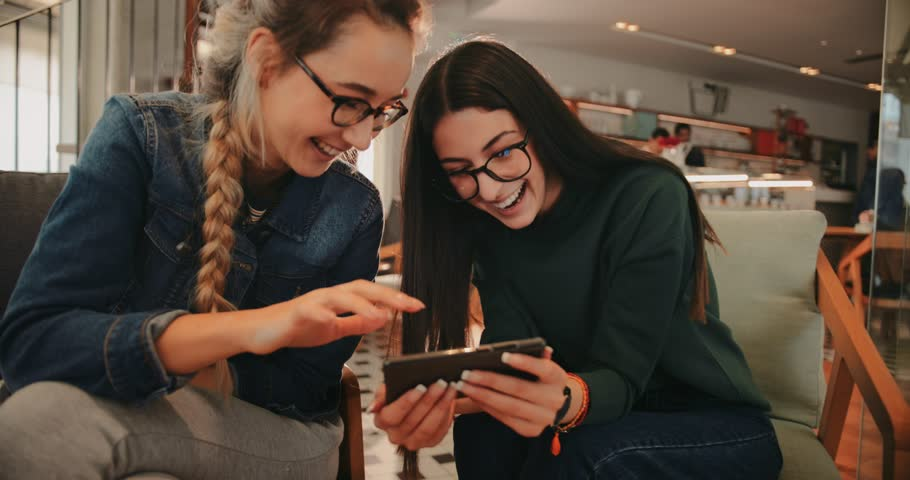 Young female friends having fun watching videos online using smartphone at coffee shop