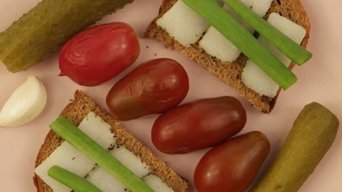 A plate with traditional Ukrainian snacks: black bread, green onions, lard, pickled tomatoes and cucumbers, garlic