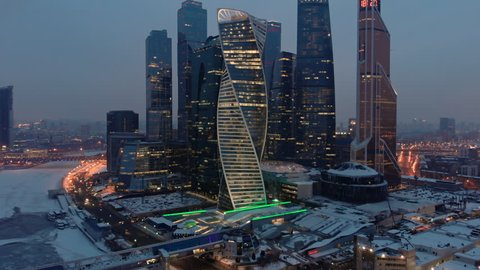 """Late evening aerial shot of Moscow-city business towers with illuminated windows and Bagration bridge over the frozen river Moskva. The iridescent """"Evolution"""" tower in the foreground."""