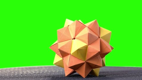 Modular origami ball on green screen. 3d modular origami flower on chroma key background. How to make decorative paper figures.