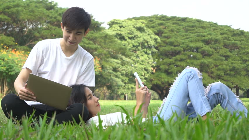 Slow motion shot of happy asian couple having fun in university park with laptop computer and mobile phone connected to wireless network. Concept of freedom youth lifestyle and technology.