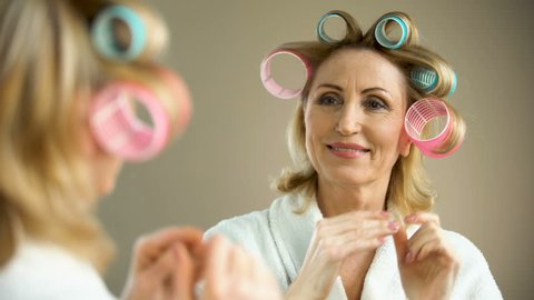 Beautiful aged lady putting hair curler and smiling into mirror, beauty tricks