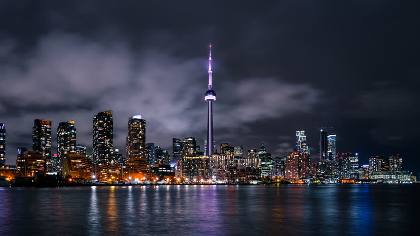 The downtown Toronto Canada city skyline with bright lights and moody storm clouds viewed from the porter island. Fast moving clouds in the sky in a quick paced urban environment.  | Shutterstock HD Video #1010445458