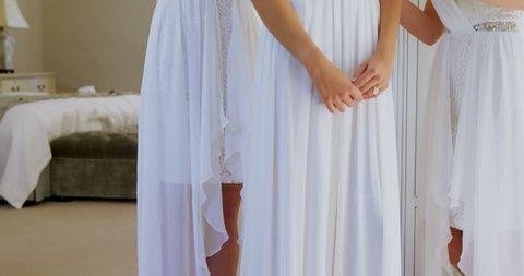 Happy bridesmaids wearing head wreath and getting bride ready in bedroom 4K 4k