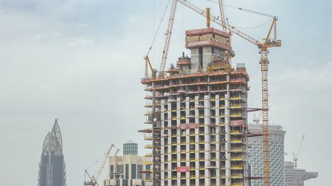 Construction site in Dubai timelapse, United Arab Emirates. Yellow cranes and workers in uniform. Aerial top view