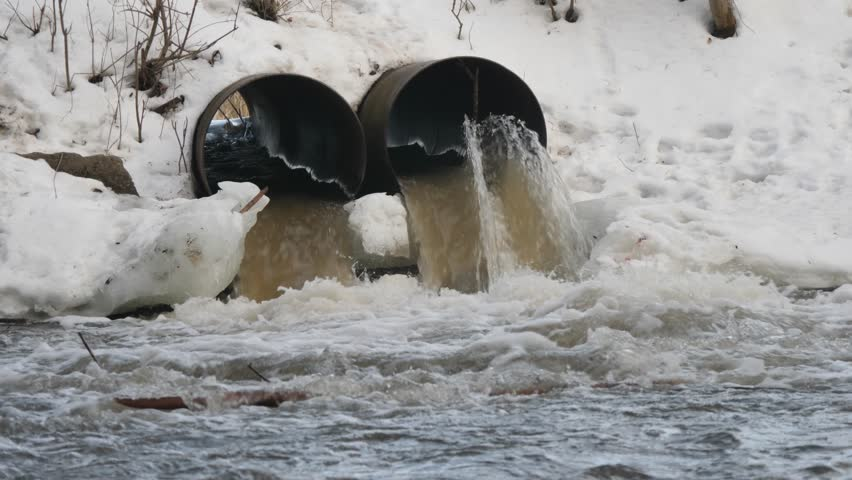 Pollution drain flowing stream to a river