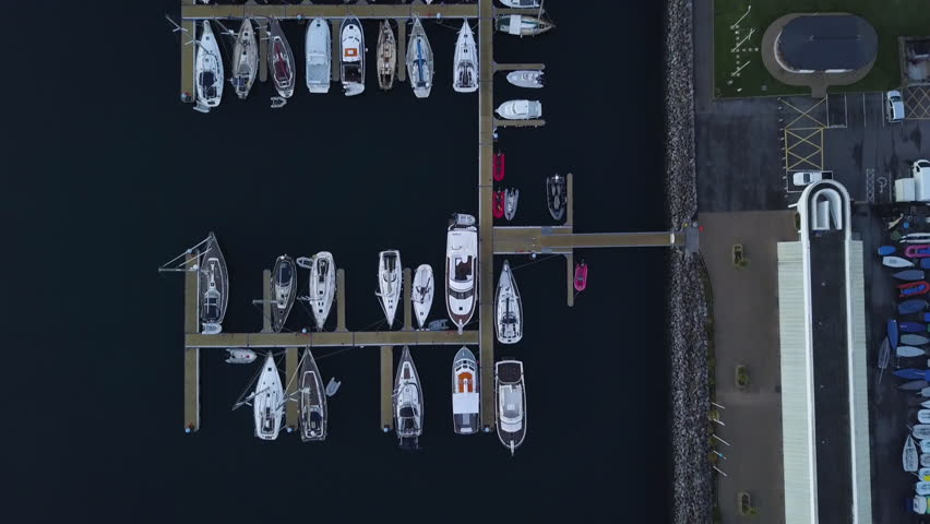 Morning Bird's Eye View Aerial Drone Shot of Sailboats in Harbour in Dingle, Ireland. Dark Blue Water and Multiple Boats of a Small European City   Shutterstock HD Video #1010456408