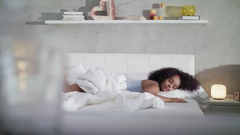 Young African American woman waking up at home. Portrait of happy black girl smiling, enjoying a large king size mattress all for herself. Slow motion