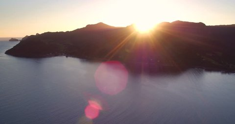 Drone shot panning over the sun cresting over the mountains in Huia near Auckland New Zealand