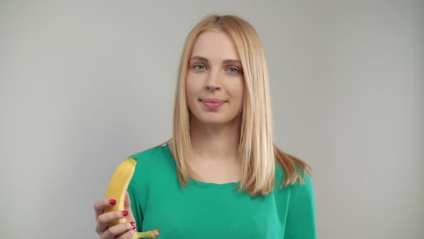 Close of blond woman eating banana at white background. Portrait of blonde girl biting ripe fruit at studio. Vegan woman eating organic food